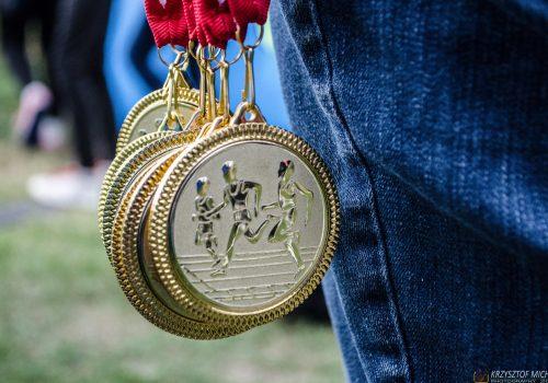 Na zdjęciu pęczek medali i fragment spodni osoby, która je trzyma.
