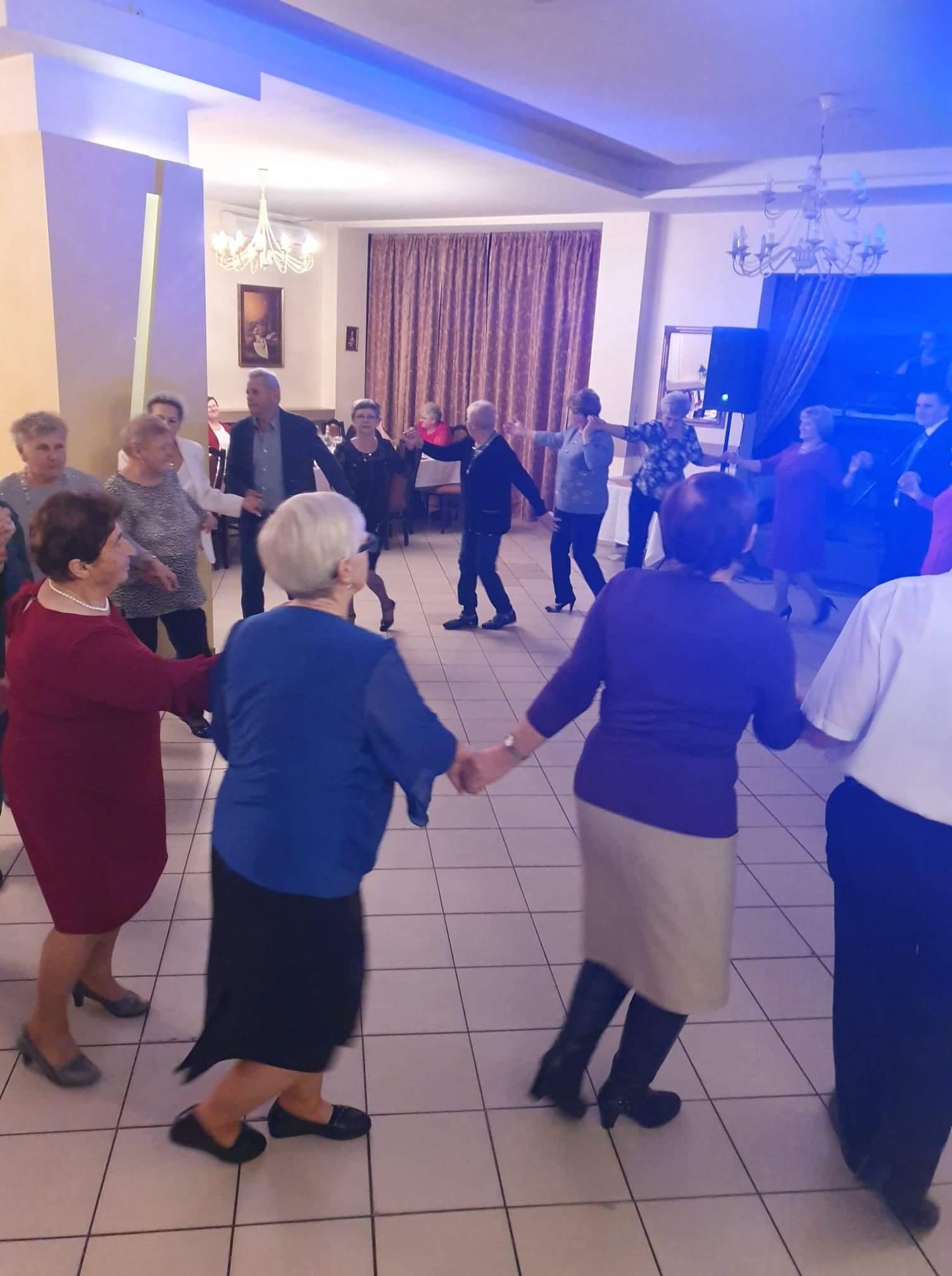 Dzień Seniora w Sołectwie Napachanie-Dalekie. Tańczący w kółku seniorzy trzymający się za ręce.