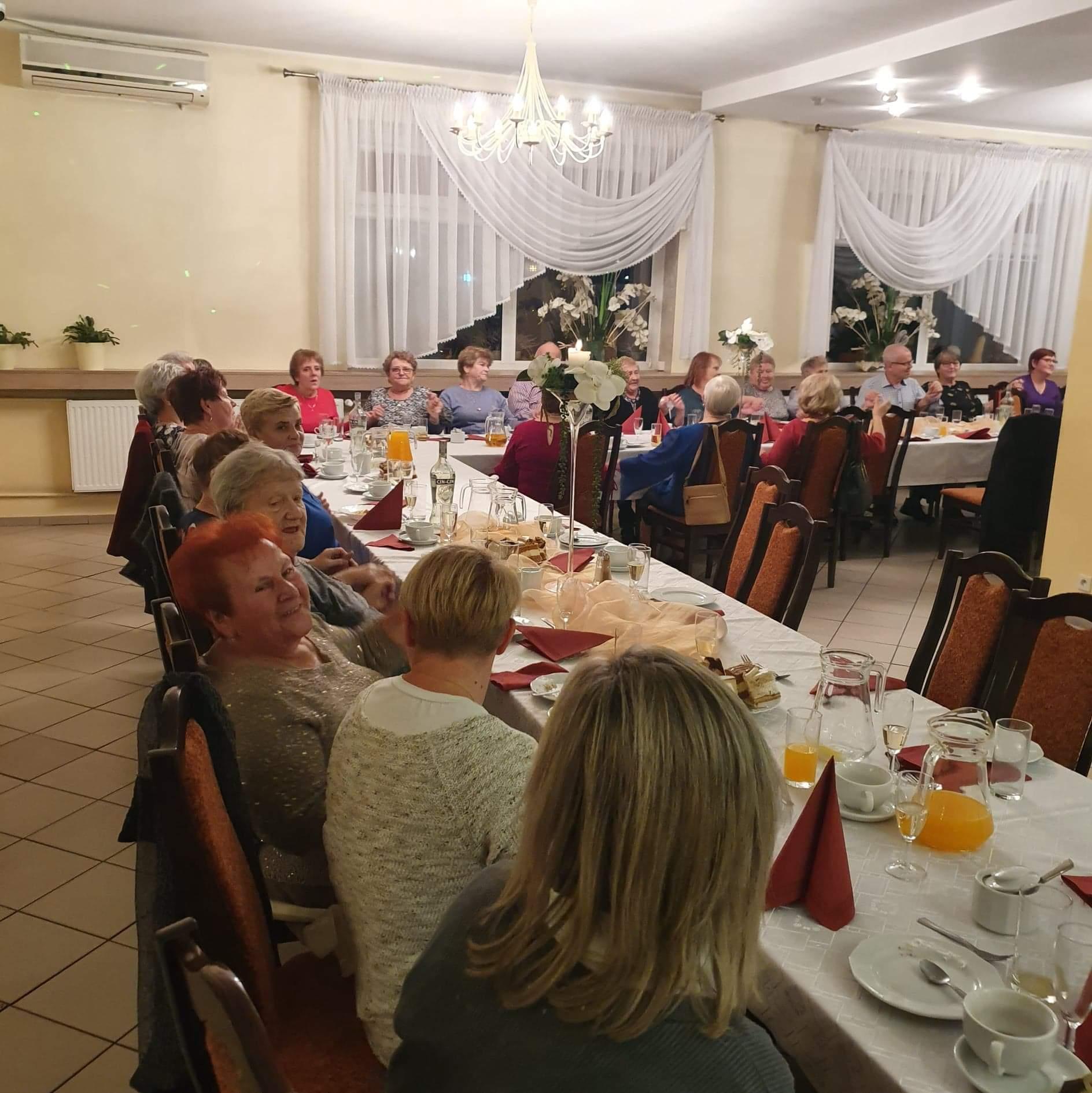 Dzień Seniora w Sołectwie Napachanie-Dalekie. Seniorzy siedzący przy stole.