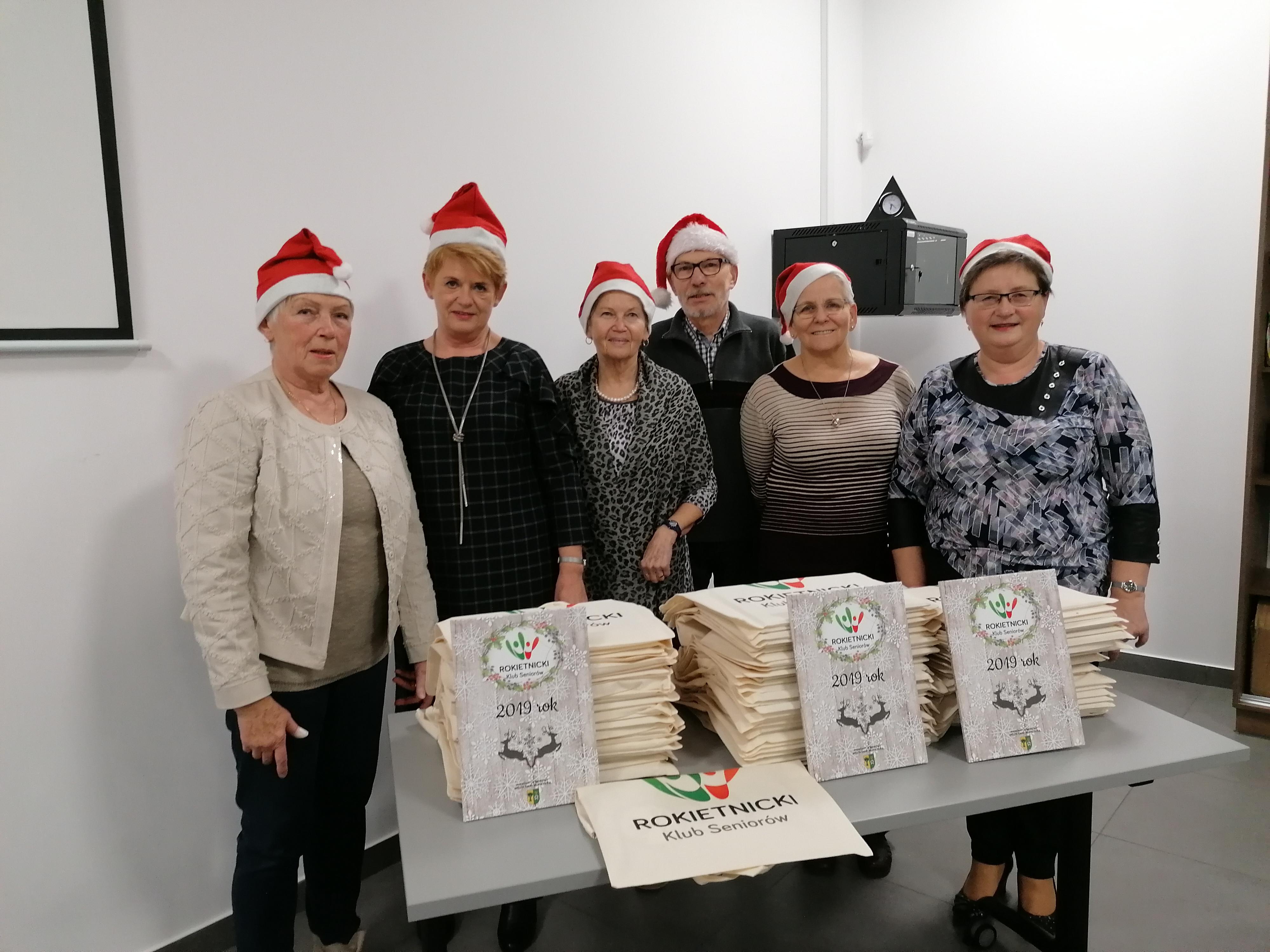 Członkowie Rokietnickiego Klubu Seniorów w mikołajkowych czapkach prezentujący puublikację - foto książkę oraz bawełniane torby znajdujące się na stole.