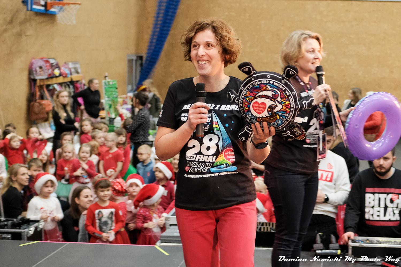Na zdjęciu na pierwszym planie Anna Jarczyńska prowadząca licytację, trzymająca w ręku poduszkę w kształcie steru. Na drugim planie druga prowadząca przy mikrofonie. W tle pod sceną dzieci przygotowujące się do występu ubrane w czerwone mikołajkowe stroje.