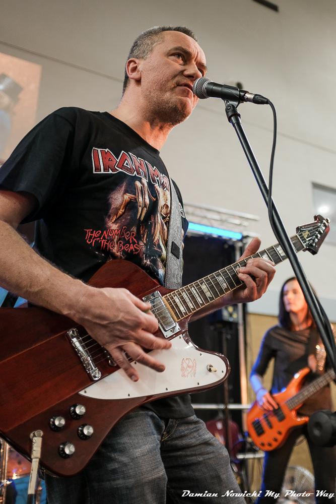 Członek zespołu Dead Pixels przy mikrofonie, grający na gitarze.
