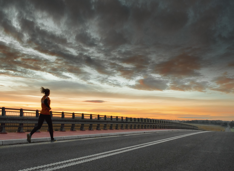Kobieta biegnąca drogą w Pawłowicach. W tle wschodzące słońce i zachmurzone niebo.