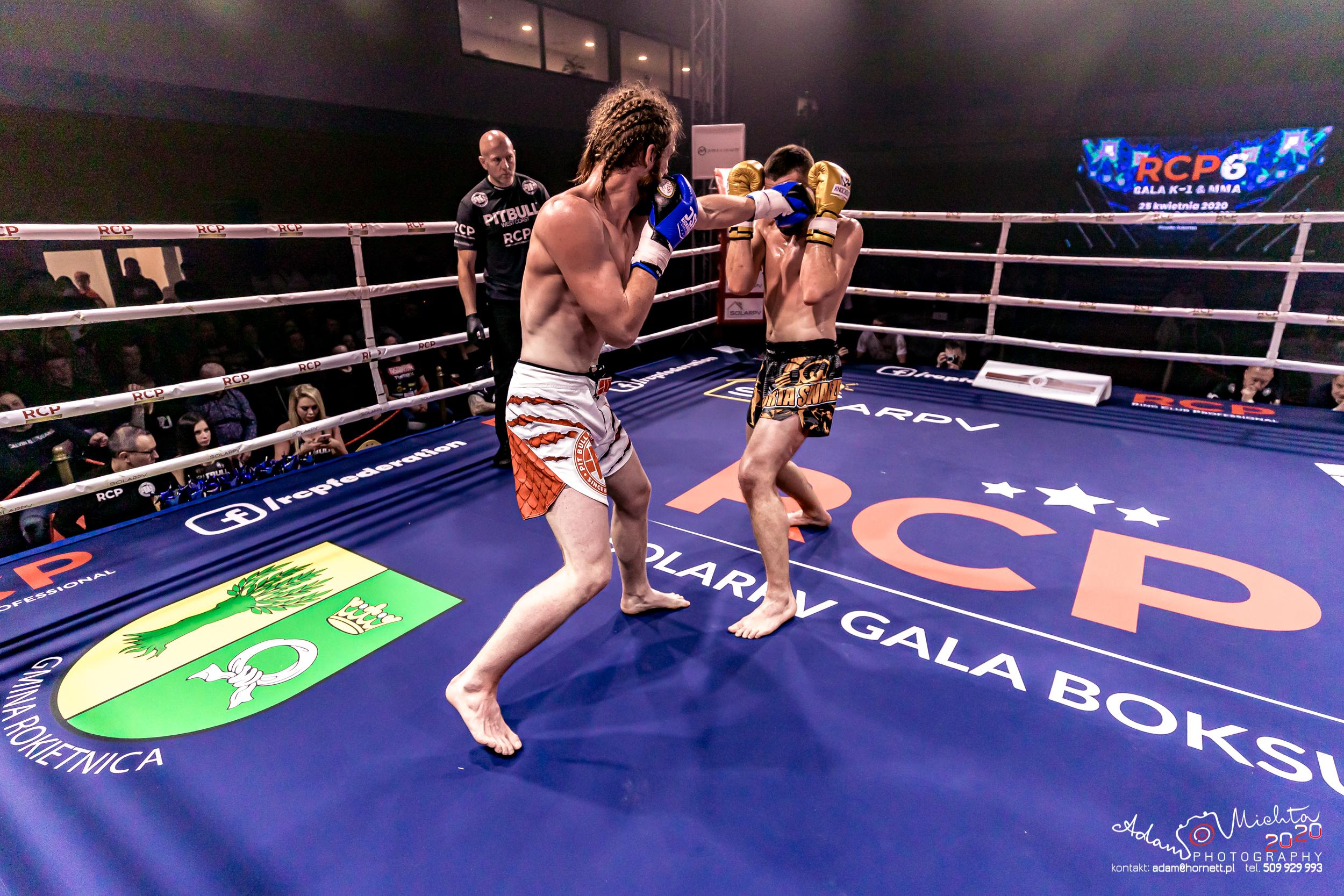 Na zdjęciu zawodnicy na ringu podczas walki. Zawodnik z prawej przyjmuje cios od przeciwnika. Sędzia się przygląda. W tle widzowie. Na ringu herb gminy Rokietnica.