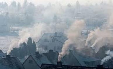 Na zdjęciu widać kilka domów z kominami, z których wydobywa się dym. Powietrze jest zanieczyszczone i ogranicza widoczność. Zdjęcie podejmuje temat smogu.