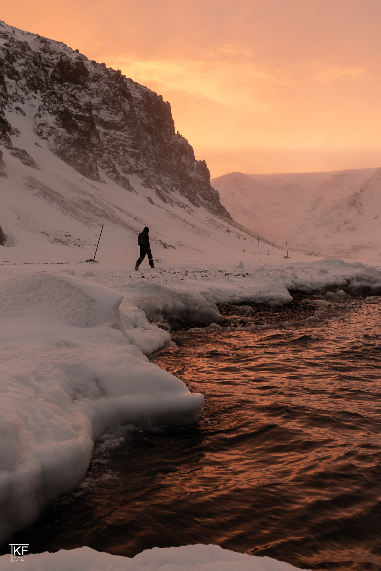 Na zdjęciu idący mężczyzna, dookoła pokrywa śnieżna, i woda, w której odbija się wieczorne, pomarańczowe światło, niebo również w kolorze pomarańczowym.