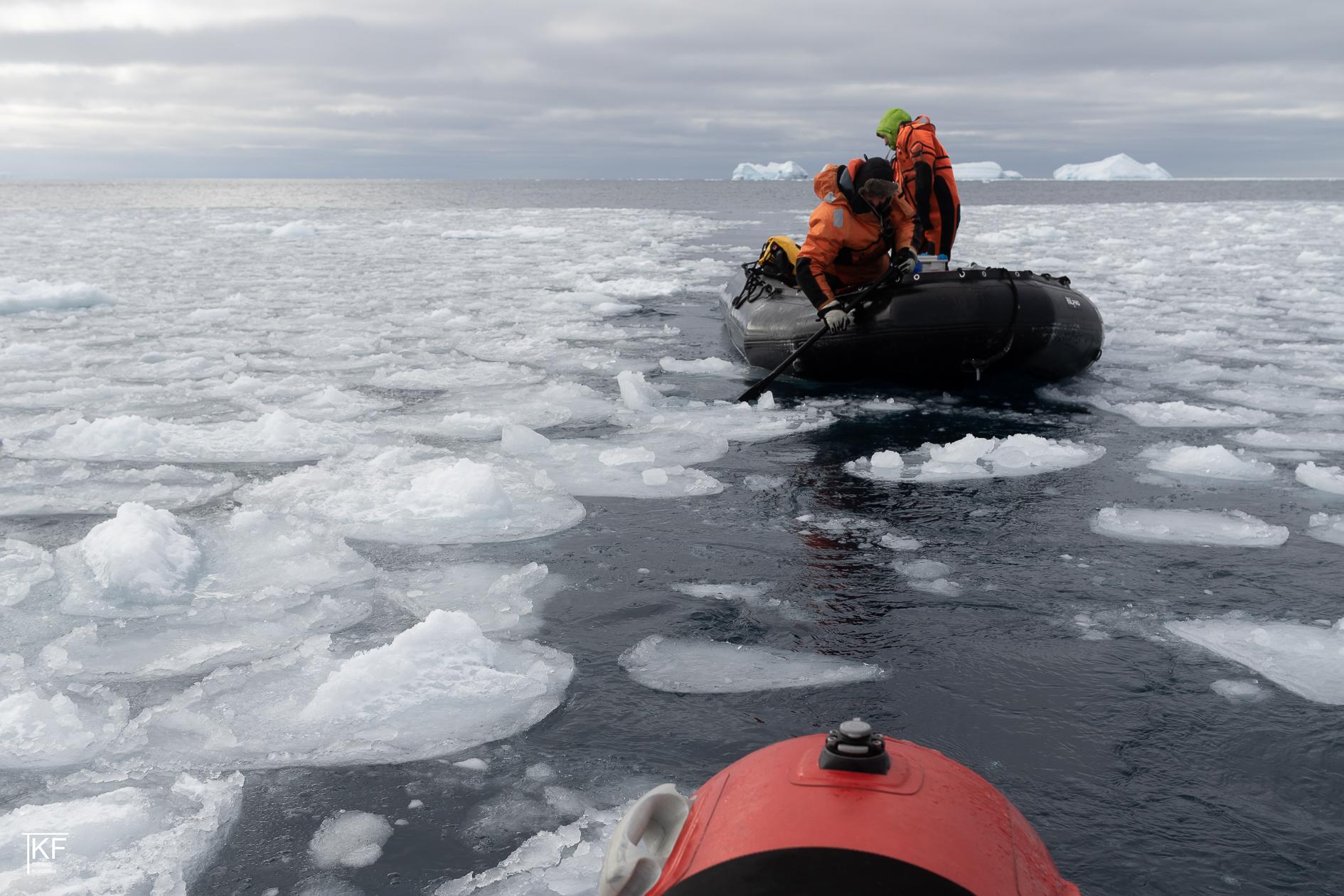 Na zdjęciu dwóch mężczyzn ubranych na czerwono i noszących kamizelki odblaskowe, płynących pontonem po częściowo zamarzniętej wodzie. Zdjęcie widziane z perspektywy osoby płynącej na pontonie za nimi. Autor Tomasz Kurczaba