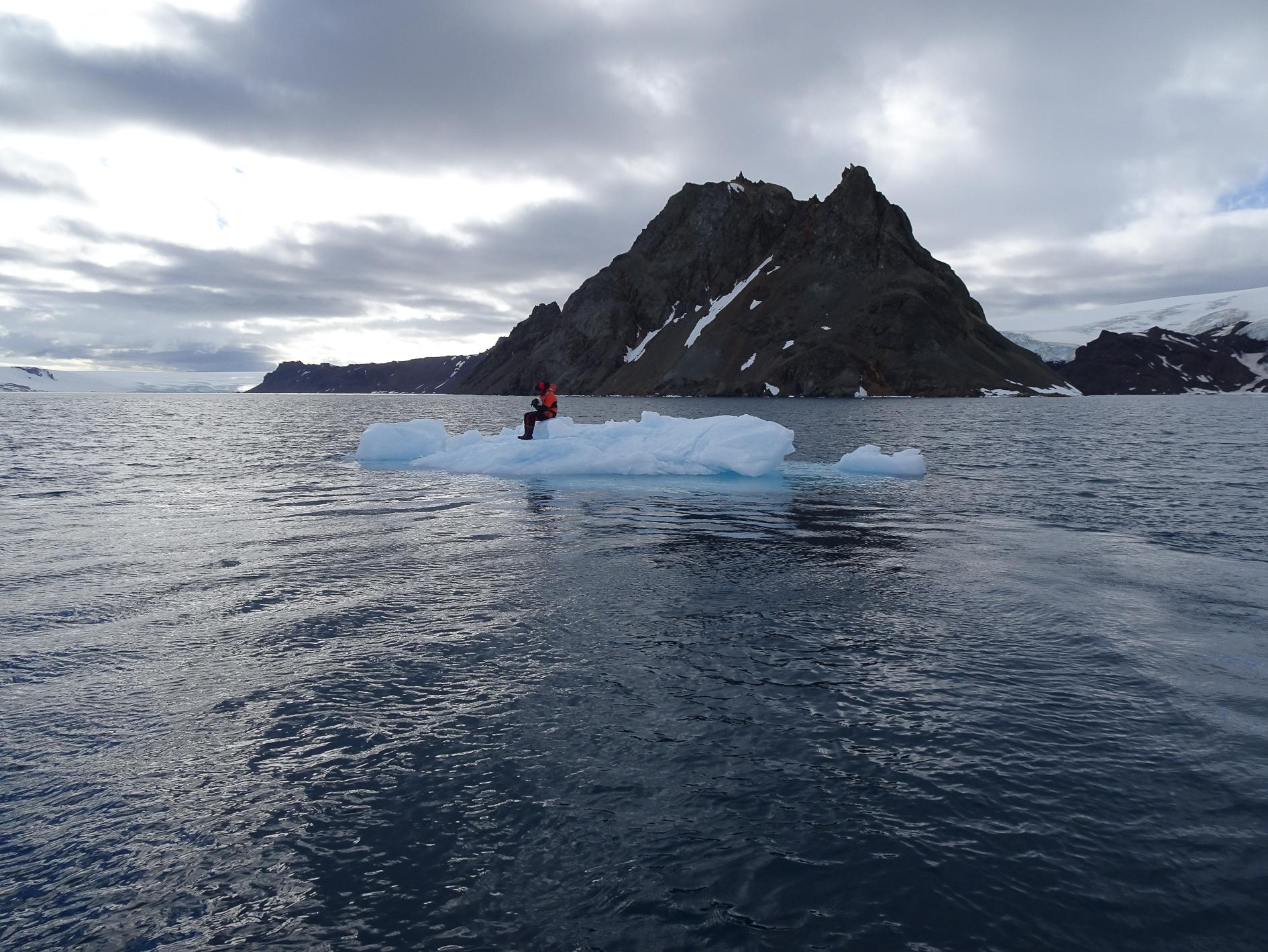 Na zdjęciu mężczyzna siedzący na krze lodowej znajdującej się na wodzie. Za nim wzgórze oraz niebo. Autor Tomasz Kurczaba