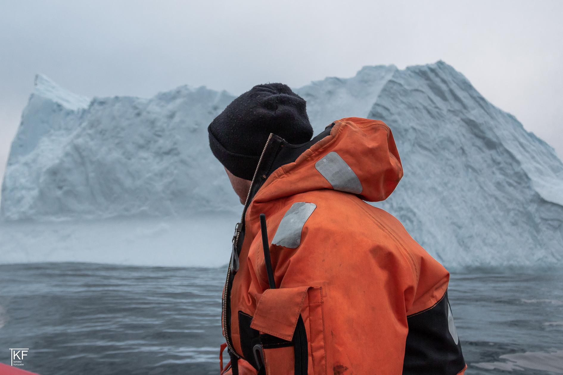 Na zdjęciu widoczny mężczyzna w pomarańczowej kurtce i czarnej czapce spoglądający w stronę wzgórza pokrytego śniegiem. Autor Tomasz Kurczaba