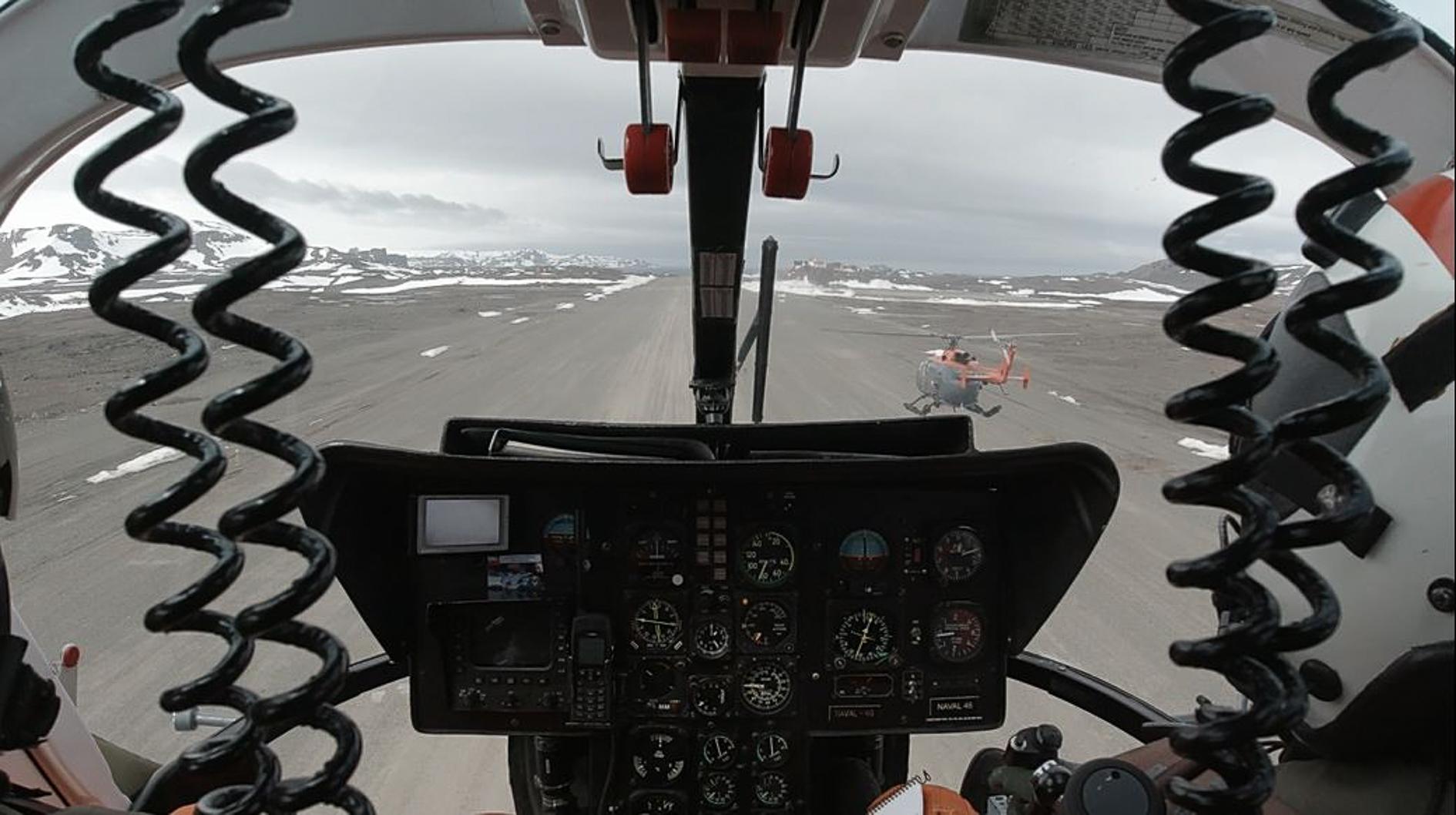 Na zdjęciu widok z kabiny pilota z kokpitem. Przed -helikopter, po lewej i prawej stronie ziemia i wzgórza pokryte śniegiem. Autor Tomasz Kurczaba