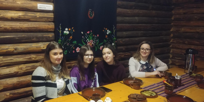 Na zdjęciu 2 uczennice Szkoły Podstawowej im. Jana Brzechwy w Rokietnicy, a jednocześnie uczestniczki projektu Erasmus+oraz dwie inne uczennice przy stole w restauracji przed podaniem posiłku.
