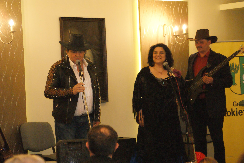 """Dzień seniora w Sołectwie Mrowino-Cerekwica. Na zdjęciu członkowie zespołu muzyczno - tanecznego """"Vanessa i Sorba"""". Kobieta i mężczyzna stoją przed mikrofonem, mężczyzna z gitarą stoi nieco z tyłu."""