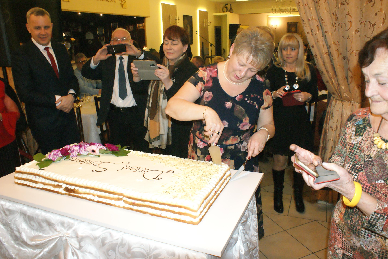 Dzień seniora w Sołectwie Mrowino-Cerekwica. Na zdjęciu Sołtys Sołectwa M rowino-Cerekwica Róża Lubka podczas krojenia tortu. Obok niej goście.