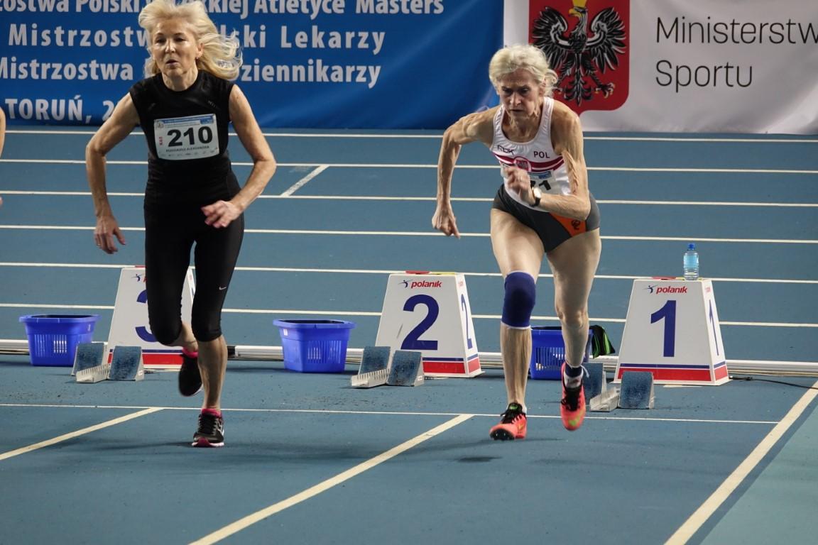 Na zdjęciu dwie zawodniczki krótko po starcie, na torze pierwszym i drugim. W tle banery - Mistrzostw i Ministerstwa Sportu.
