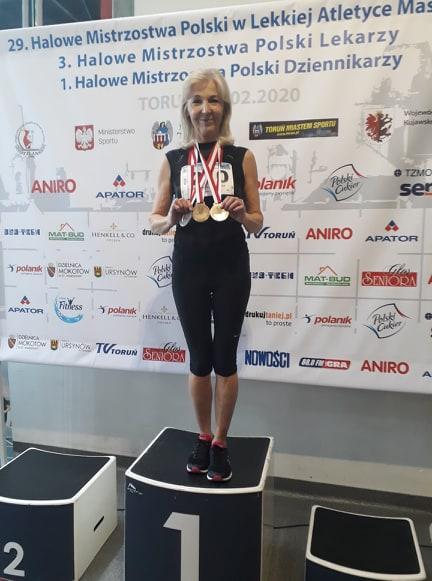 Na zdjęciu pani Aleksandra Podsiadło stojąca na pierwszym miejscu podium i prezentująca zdobyte medale: 2 złote i 1 srebrny. Za jej plecami banery zawodów z nazwą imprezy i logotypami organizacji.