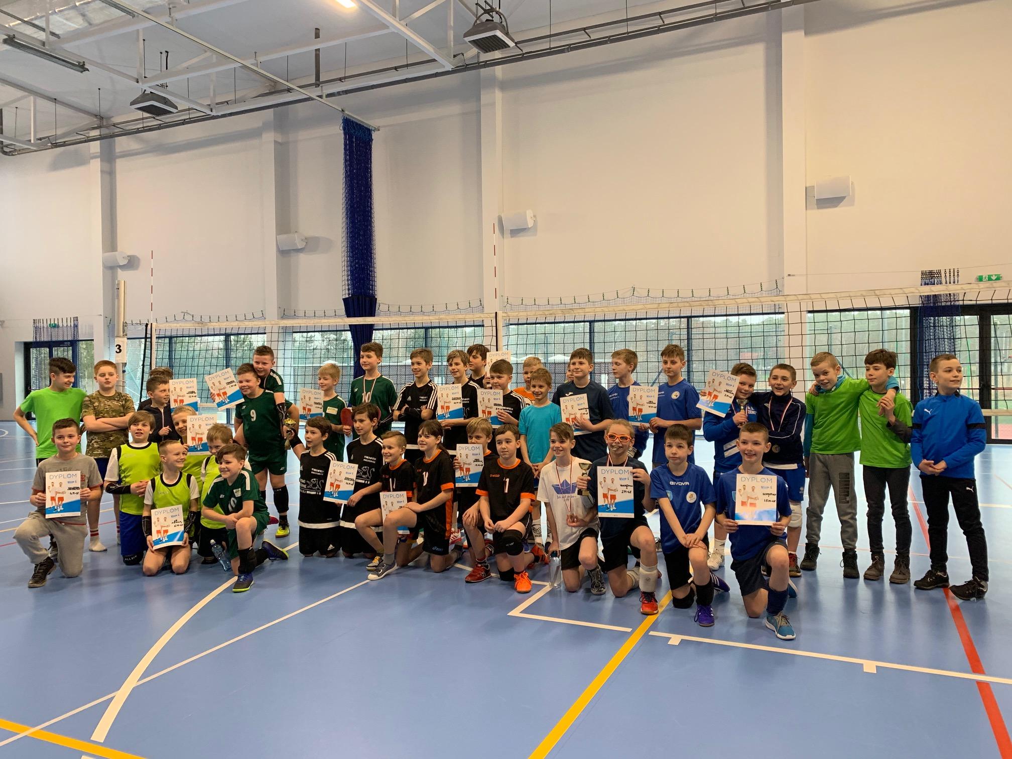 Na zdjęciu znajdują się uczestnicy turnieju Mini Lider Cup w hali Zeposłu Szkolno-Przedszkolnego w Napachaniu, chłopcy prezentujący puchary i dyplomy.