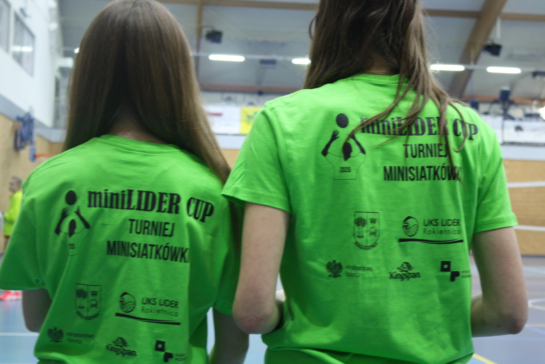 Na zdjęciu znajdują się dwie dziewczynki stojące tyłem do obiektywu. Mają na sobie zielone koszulki z napisem miniLIDER CUP TURNIEJ MINISIATKÓWKI, rysunkiem siatkarza i logotypami organizatorów i sponsorów: Gmina Rokietnica, UKS Lider, Ministerstwo Sportu, Kingspan, Powiat Poznański.