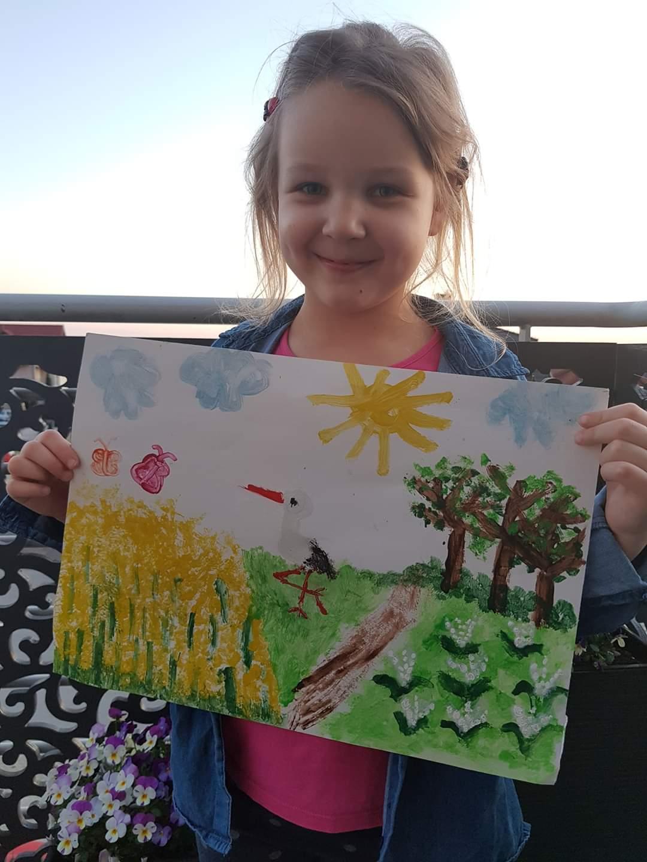 Na zdjęciu widoczna uśmiechnięta dziewczynka prezentująca namalowany przez siebie obraz. Na nim znajduje się wiosenny krajobraz - łąka, drzewa, kwiaty, bocian, rzepak, niebo, słonce, chmury i motyle.
