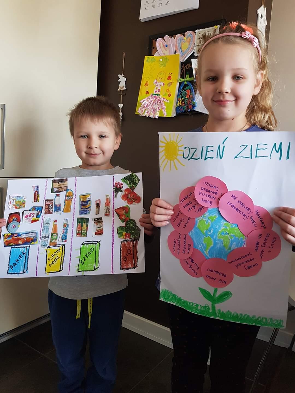 Na zdjęciu widoczne uśmiechnięte dzieci - dziewczynka i chłopiec prezentujący swoje prace nt. Dnia Ziemi. Na kolażu chłopca zasady segregacji odpadów, na pracy dziewczynki - kula ziemska w postaci kwiatka, jako płatki zasady przyczyniające się do ochrony środowiska i zasobów naturalnych.