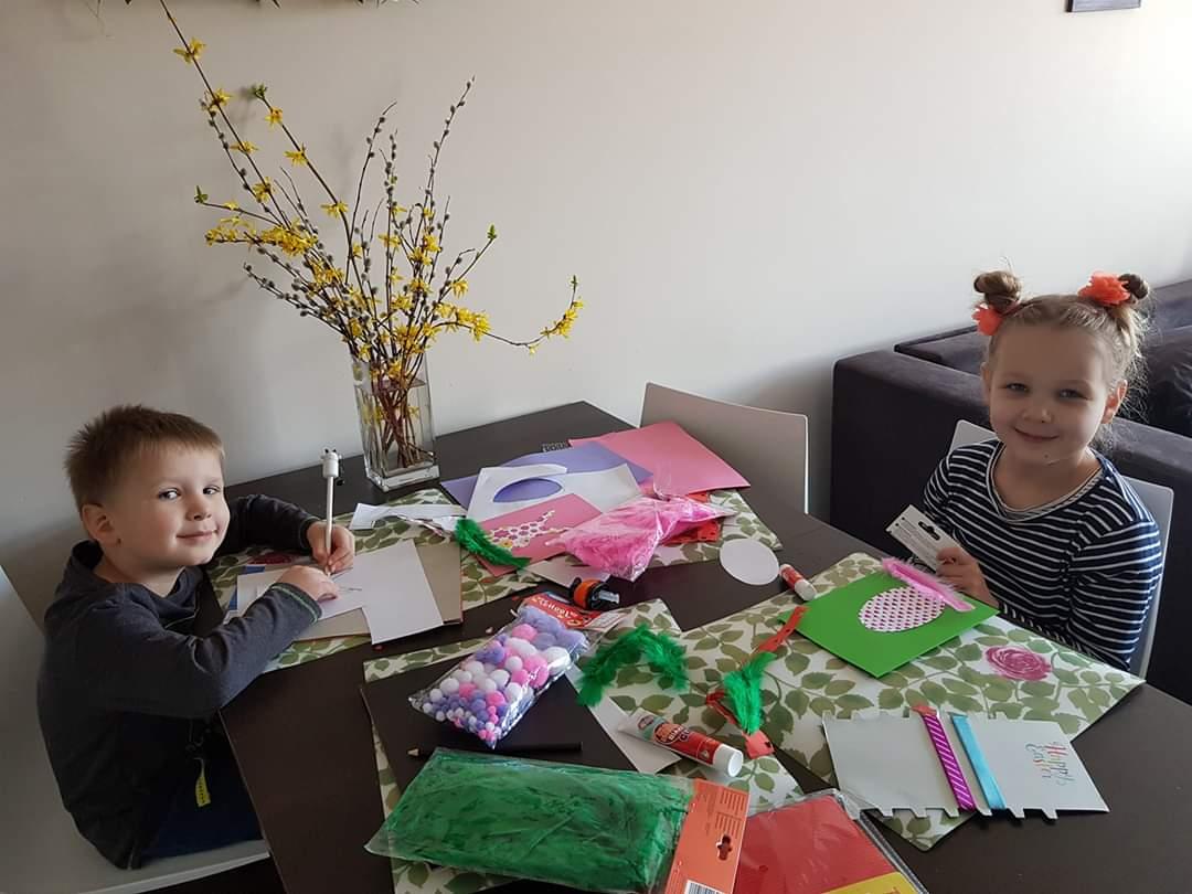 Na zdjęciu uśmiechnięte dzieci - dziewczynka i chłopiec siedzący przy stole naprzeciwko siebie. Na stole widoczne kartki papieru i ozdoby.