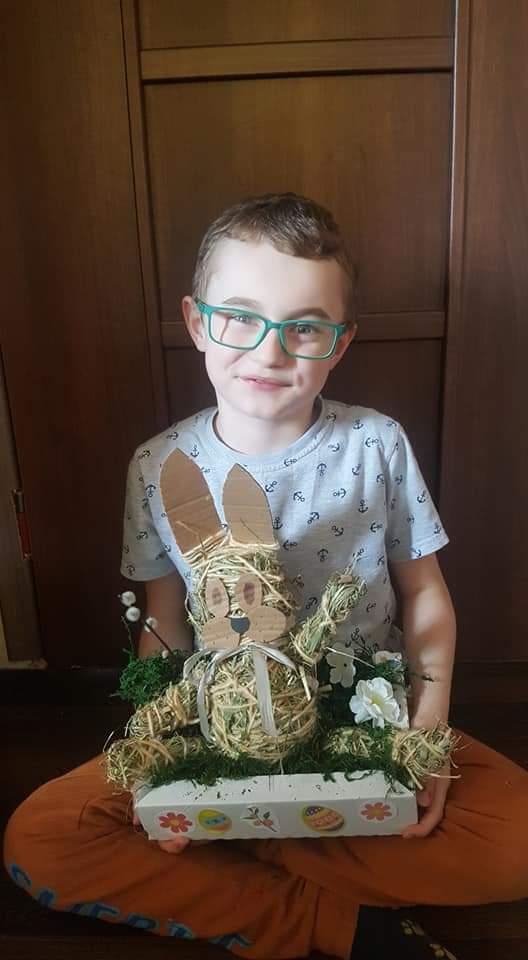 Na zdjęciu uśmiechnięty chłopiec, trzymający na kolanach ozdobę - wielkanocnego zajączka.