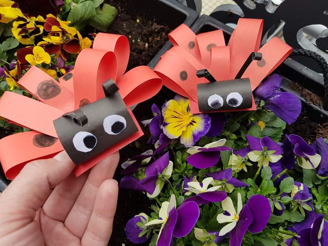 Na zdjęciu dwie papierowe biedronki. W tle kwiaty - bratki.