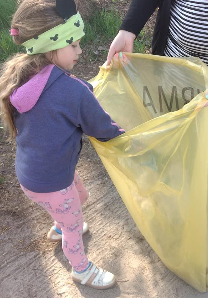 Na zdjęciu dziewczynka wrzucająca śmieci do żółtego worka, który trzyma rodzic.