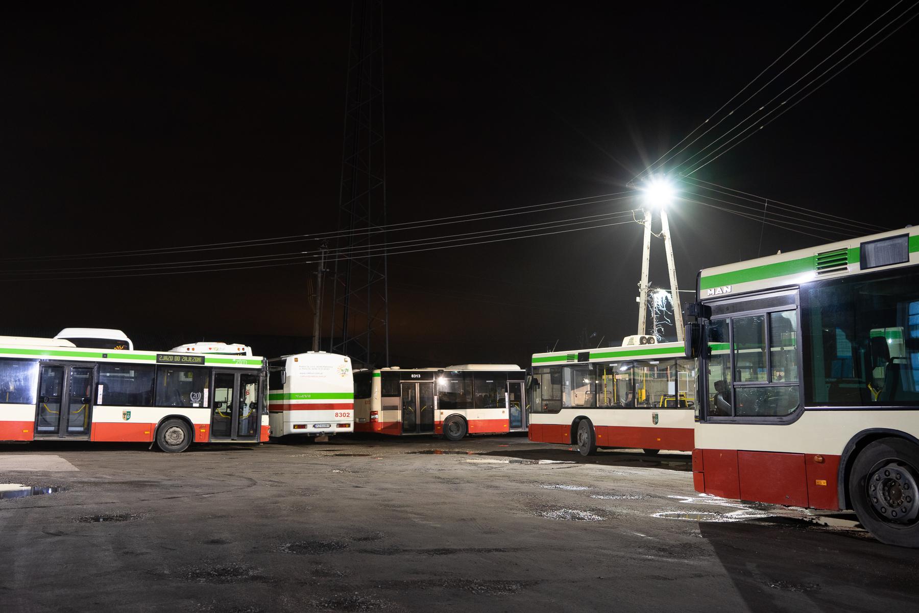 Na zdjęciu pięć pojazdów Rokbus - cztery autobusy i autokar na parkingu przed dawną bazą. Widok wieczorem, rozświetla go latarnia. Autor: Piotr Surmiński.