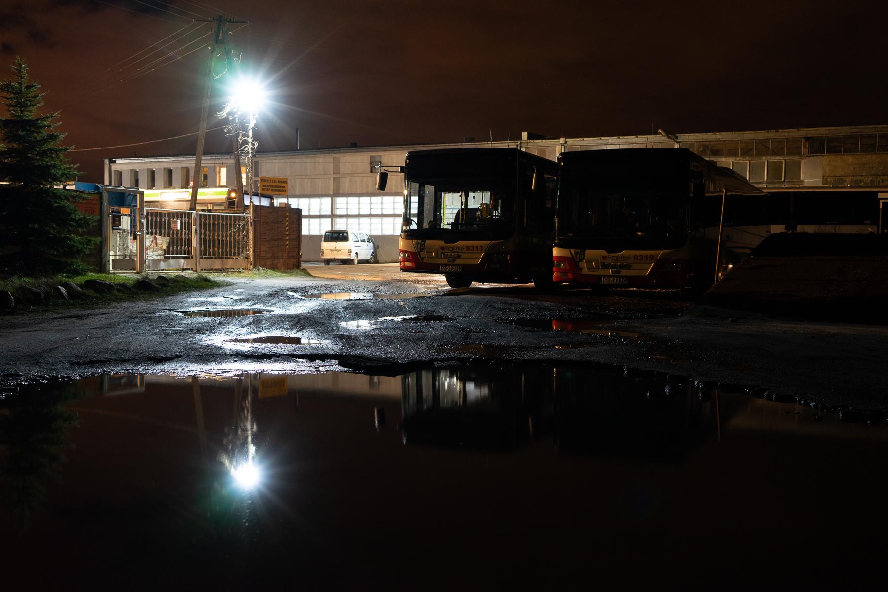Na zdjęciu dawna baza Rokbusu wieczorem. Na zewnątrz dwa autobusy. Widok rozświetla latarnia. Autor: Piot Surmiński.