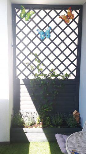 Na zdjęciu widoczna jest boczna ściana balkonu ustrojona drewnianymi motylami. Na dole ściany umieszczona została donica z roślinami.