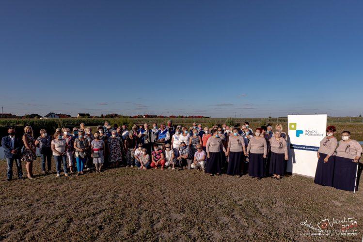 Na zdjęciu widać dużą grupę seniorów, stojących na polu w słoneczny dzień