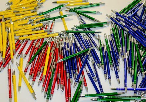 Na zdjęciu stos długopisów w kolorze żółty, zielonym, czerwonym i niebieskim z napisem Szkoła Podstawowa w Cerekwicy. Fot. Damian Nowicki