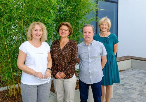 Na zdjęciu nauczyciele szkoły podstawowej w Cerekwicy - trzy kobiety i mężczyzna pozujący na tle roślinności. Fot. Damian Nowicki