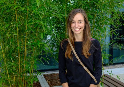 Na zdjęciu uśmiechnięta, około 30-letnia kobieta pozująca na tle roślinności w szkole podstawowej w Cerekwicy. Fot. Damian Nowicki.