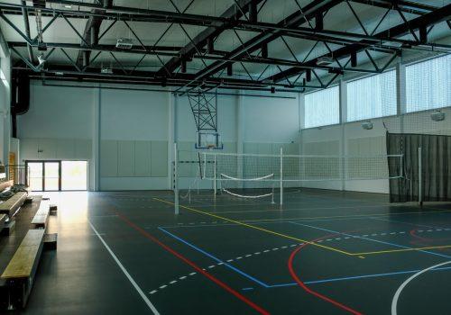 Na zdjęciu sala gimnastyczna szkoły podstawowej w Cerekwicy. Widoczna jest bramka, siatki do gry w siatkówkę oraz tenisa, a także trybuny. Fot. Damian Nowicki