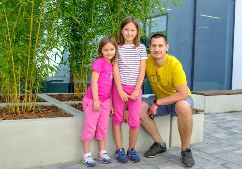 Na zdjęciu mężczyzna i dwie dziewczynki pozujące na tle roślinności w szkole podstawowej w Cerekwicy. Fot. Damian Nowicki.