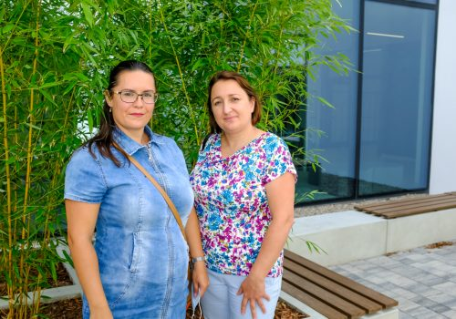Na zdjęciu dwie około 40-letnie kobiety pozujące na tle roślinności w szkole podstawowej w Cerekwicy. Fot. Damian Nowicki.