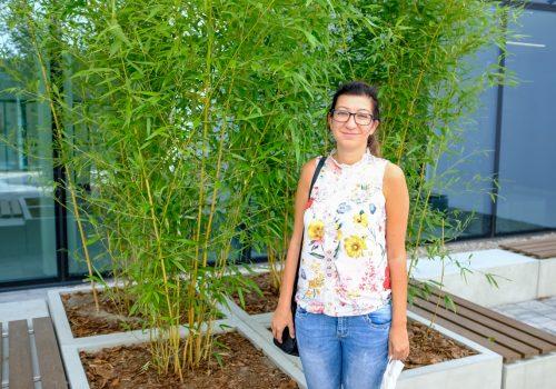 Na zdjęciu około 40-letnia kobieta pozująca na tle roślinności w szkole podstawowej w Cerekwicy. Fot. Damian Nowicki