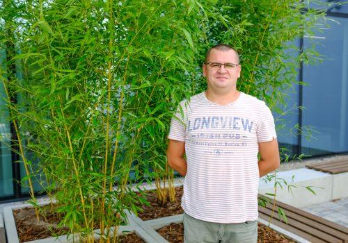 Na zdjęciu około 40-letni mężczyzna pozujący na tle roślinności w szkole podstawowej w Cerekwicy. Fot. Damian Nowicki