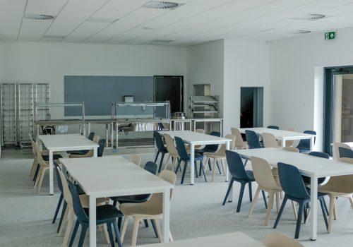 Na zdjęciu wnętrze klasy w szkole podstawowej w Cerekwicy, a w niej białe stoliki, granatowe i beżowe krzesła oraz regały. Fot. Damian Nowicki