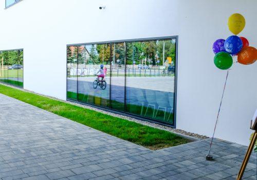 Na zdjęciu szkoła podstawowa w Cerekwicy z zewnątrz. W jednym z okien widoczne odbicie dwóch dziewczynek, z których jedna jeździ rowerem oraz stojaków na rowery. Z prawej strony okna kolorowe balony. Fot. Damian Nowicki