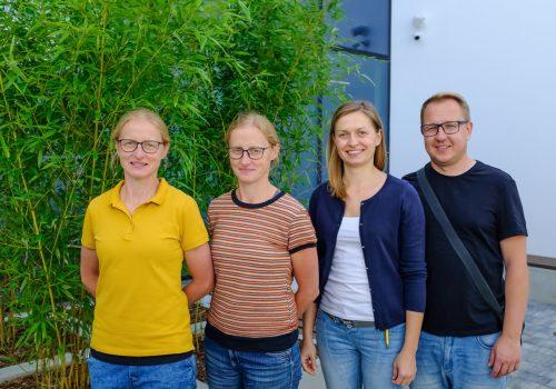 Na zdjęciu trzy siostry w wieku około 30-40 lat oraz mężczyzna pozujący na tle roślinności w szkole podstawowej w Cerekwicy. Fot. Damian Nowicki