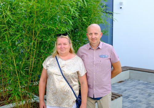 Na zdjęciu około 40-letnia para pozująca na tle roślinności w szkole podstawowej w Cerekwicy. Fot. Damian Nowicki