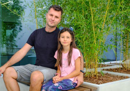 Na zdjęciu mężczyzna oraz dziewczynka pozujący na tle roślinności w szkole podstawowej w Cerekwicy. Fot. Damian Nowicki