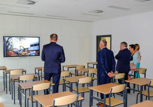 Na zdjęciu wnętrze klasy szkoły podstawowej w Cerekwicy, a w niej szkolne ławki i krzesła oraz 5 osób oglądających film z powstawania szkoły wyświetlany na ekranie telewizora. Fot. Damian Nowicki