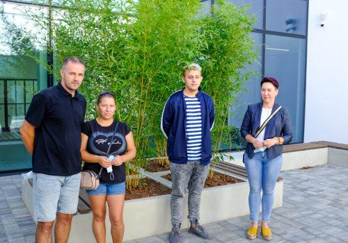 Na zdjęciu 4 osoby - dwóch mężczyzn i dwie kobiety, zwiedzający szkołę podstawową w Cerekwicy, pozujący na tle roślinności. Fot. Damian Nowicki