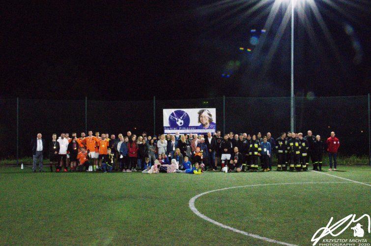 Na zdjęciu widać dużą liczbę osób pozujących do zdjęcia późnym wieczorem na płycie boiska ORLIK w Napachaniu. Na siatce boiska nad zebranymi rozwieszony jest billboard Turnieju Piłkarskiego im. Marcina Matysiaka z jego podobizną.