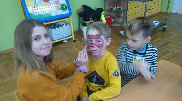 """Na zdjęciu młoda dziewczyna malująca twarz chłopcu w przedszkolu """"Bajeczka"""" w Rokietnicy. Oboje patrzą w kierunku fotografa. Obok siedzi drugi chłopiec i patrzy w bok. Autor: Stowarzyszenie CREO"""