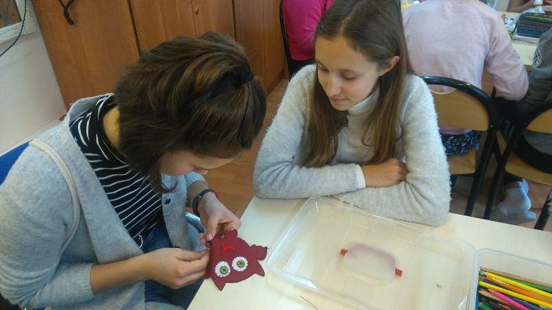 Na zdjęciu dwie młode dziewczyny siedzące przy szkolnej ławce w Zespole Szkół nr 109 przy Ośrodku Rehabilitacyjnym dla Dzieci w Poznaniu-Kiekrzu. Jedna z nich wyszywa kształt sowy. W tle inni uczestnicy. Autor:Stowarzyszenie CREO