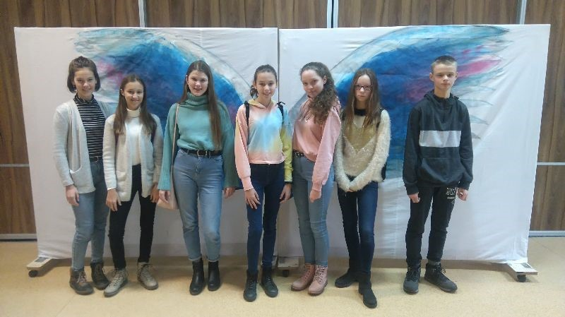 Na zdjęciu uczestnicy projektu DziałaMY, sześć młodych dziewczyn i jeden chłopak pozujący na tle planszy przedstawiającej niebieskie skrzydła, w Zespole Szkół nr 109 przy Ośrodku Rehabilitacyjnym dla Dzieci w Poznaniu-Kiekrzu. Autor: Stowarzyszenie CREO